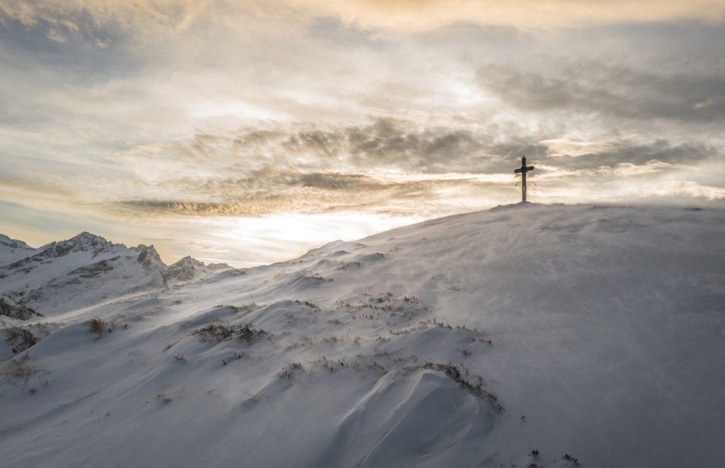 croix catholique sur une montagne enneigée